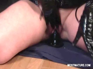mature tramp in latex riding fake penis and